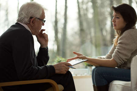 Foto de Young woman lamenting to her elderly psychologist - Imagen libre de derechos