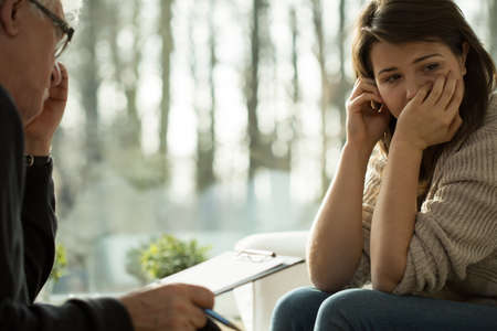 Foto de Young depressed woman taking advice from her psychologist - Imagen libre de derechos