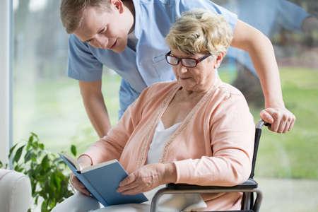 Foto de Portrait of handicapped senior woman reading book - Imagen libre de derechos