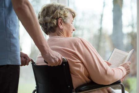 Foto de Disabled woman reading book in retirement home - Imagen libre de derechos