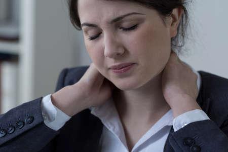 Foto de Female white-collar worker having neck pain - Imagen libre de derechos