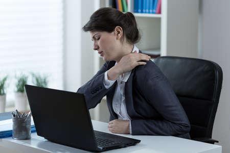 Foto de Businesswoman leading sedentary lifestyle causing back pain - Imagen libre de derechos