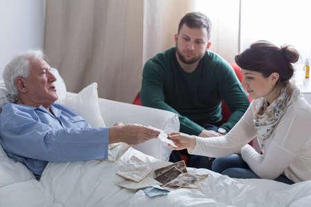 Foto de Terminally ill father remembering the past with children - Imagen libre de derechos
