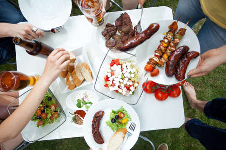 Photo for People eating grilled dishes on garden party - Royalty Free Image