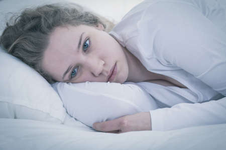 Foto de Close-up of young sad tired woman lying in bed - Imagen libre de derechos