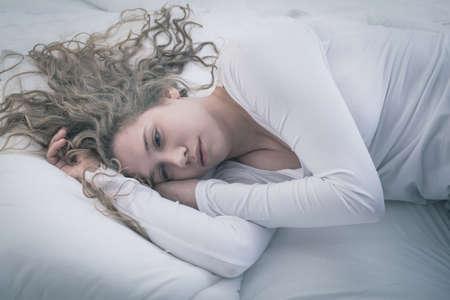 Foto de Young attractive woman in deep depression lying alone - Imagen libre de derechos