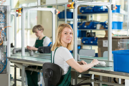 Photo pour Beauty young woman working on production line - image libre de droit