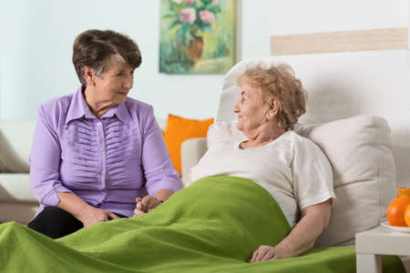 Foto de Woman visiting her sick elderly friend - Imagen libre de derechos