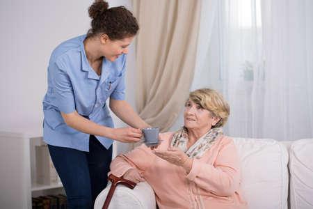 Foto de Young caregiver caring about elder lady at home - Imagen libre de derechos