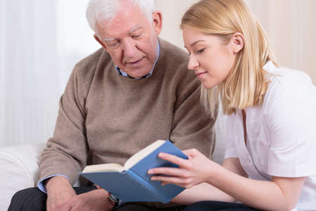 Foto de Senior man and caregiver reading interesting book - Imagen libre de derechos