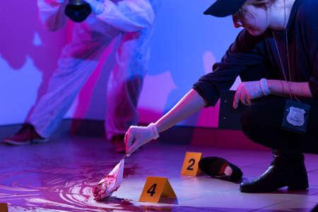 Photo pour Image of policewoman working on a murder scene - image libre de droit