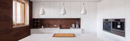Photo pour Panorama of white and brown kitchen interior - image libre de droit