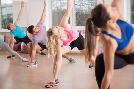 Photo pour Fitness group stretching body during fitness classes - image libre de droit