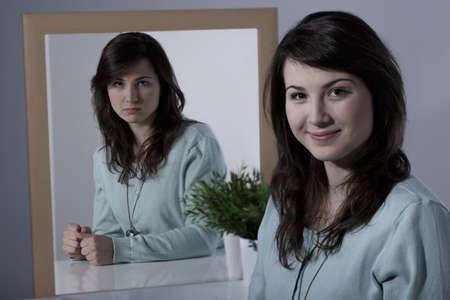 Foto de Lady with bipolar disorder sitting at the desk - Imagen libre de derechos