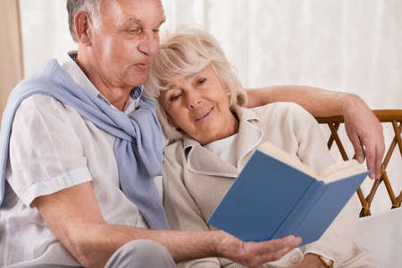 Photo pour Loving senior couple reading together interesting book - image libre de droit