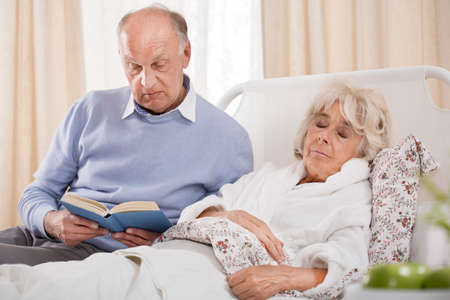 Photo pour Image of husband reading ill wife book - image libre de droit