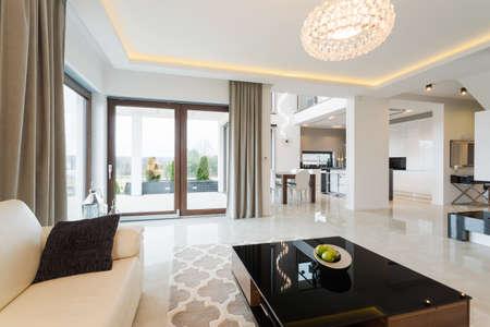 Photo pour Modern decor of enormous bright lounge with fancy coffee table - image libre de droit