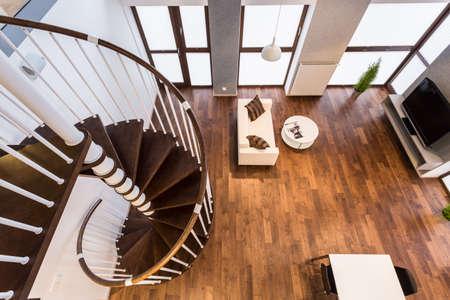 Photo pour Curve wooden stairs in spacious living room - image libre de droit