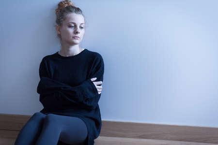 Foto de Young woman with anxiety disorder sitting on the floor - Imagen libre de derechos