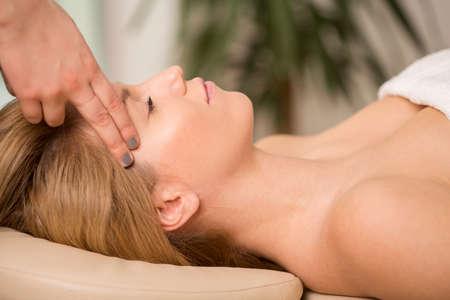 Foto de Bioenergy therapist healing young woman's headache - Imagen libre de derechos