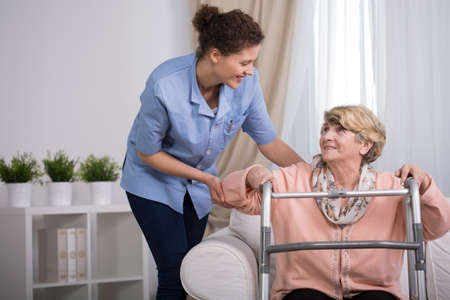 Senior injured woman with walker trying to stand up