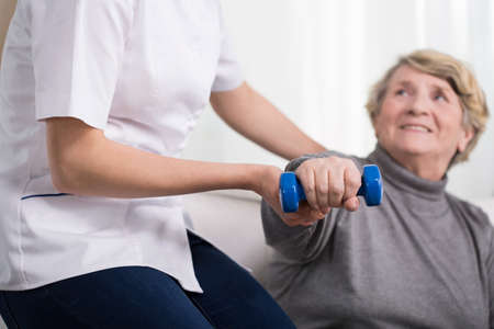 Foto de Aged exercising woman and female physiotherapist's help - Imagen libre de derechos