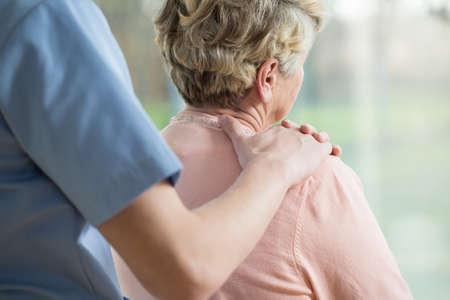Foto de Nurse putting hand on elderly woman's shoulder - Imagen libre de derechos