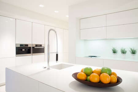 Photo pour Fruit in a bowl on the marble island in white kitchen - image libre de droit