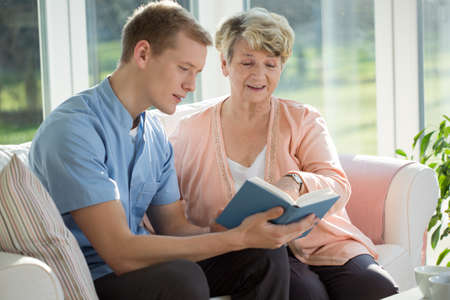 Foto de Young male nurse reading to his elderly patient - Imagen libre de derechos