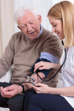 Photo pour Pretty experienced nurse measuring the older man's blood pressure - image libre de droit