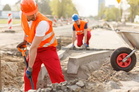 Photo pour Two hard working builders in uniforms putting pavement - image libre de droit