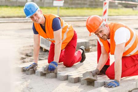Foto de Two smiling construction workers laying new cobblestones - Imagen libre de derechos