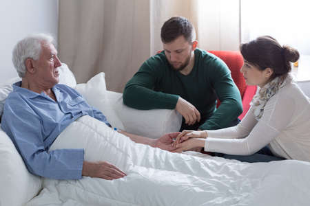 Photo pour Supportive adult kids and terminally ill dad in bed - image libre de droit