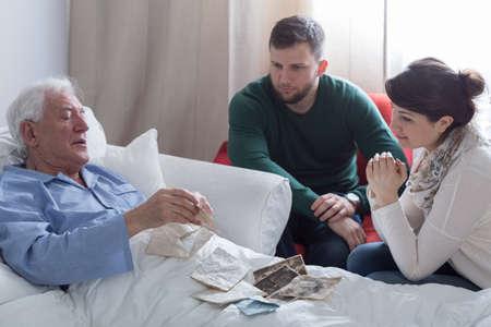 Photo pour Older sick man in hospital opening old letters - image libre de droit