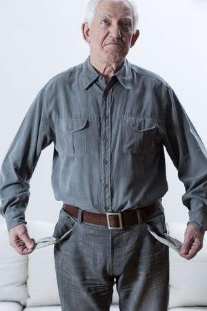Foto de Sad elderly poor man standing with empty pockets - Imagen libre de derechos