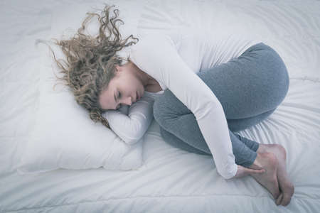 Foto de Desperate young woman curled up in bed - Imagen libre de derechos