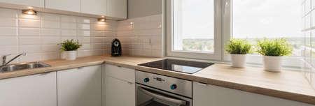 Foto de Wooden worktops and white cupboards in cozy kitchen - Imagen libre de derechos