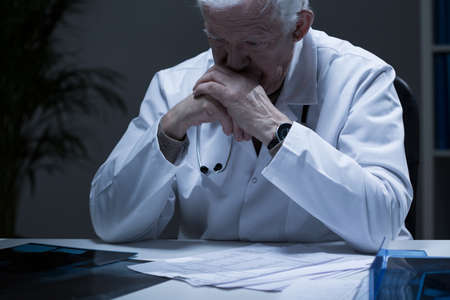 Photo pour Old doctor with deep depression crying in solitude - image libre de droit