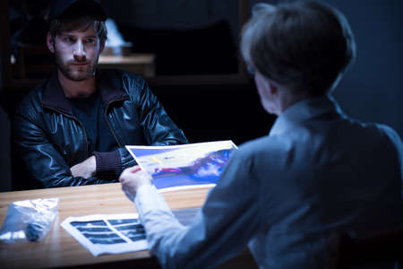 Photo pour Suspect man interview in dark interrogation room - image libre de droit
