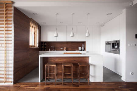 Photo pour Modern wooden kitchen with white island and dining space - image libre de droit