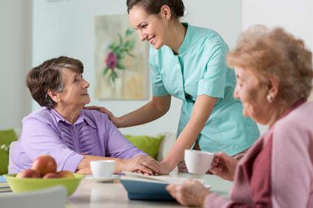 Foto de Two older women having a nice conversation with young nurse - Imagen libre de derechos