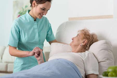 Foto de Senior woman in hospital bed holding nurse's hand - Imagen libre de derechos