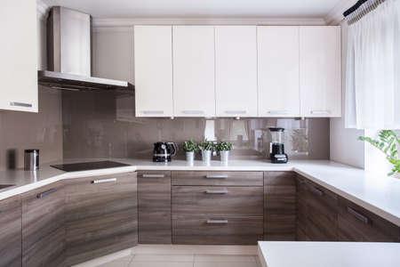 Photo pour Cozy beige kitchen interior with wooden cupboards - image libre de droit