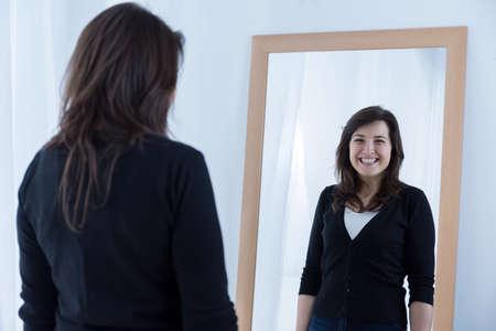 Photo pour Reflection of girl wearing a fake smile - image libre de droit