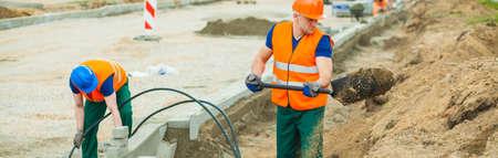 Foto de Contruction workers are digging in the electrical cables - Imagen libre de derechos