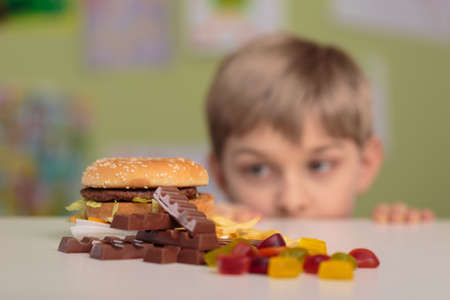 Photo pour Greedy little boy looking at unhealthy tasty snacks - image libre de droit