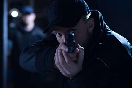 Photo pour Image of a focused policeman aiming gun during intervention - image libre de droit