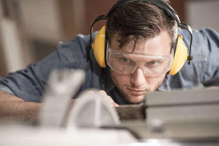 Foto de Carpenter while using electric tools wearing protective headphones - Imagen libre de derechos