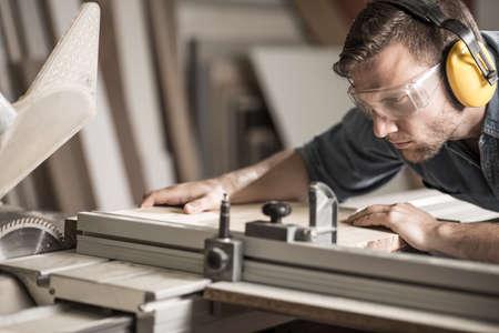 Photo pour Young attractive man doing woodwork in carpentry - image libre de droit