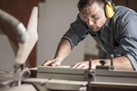 Photo pour Mature joiner using measuring machine in carpentry - image libre de droit